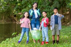 Free Group Family Asian Children Collecting Garbage And Plastic On The River To Dumped Into The Trash For Volunteer Charity Save Enviro Royalty Free Stock Photos - 156056018