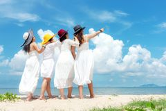 Group family asian woman wearing fashion white dress summer standing the sandy sea beach, outdoors sunshine background. royalty free stock photo