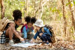 Group family children checking map for explore and find directions in the camping jungle nature and adventure