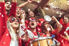 Group of fans dressed in red color watching a sports event Stock Image