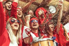 Group of fans dressed in red color watching a sports event. In the stands of a stadium royalty free stock photography
