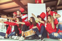 Group of fans dressed in red color watching a sports event Royalty Free Stock Photography