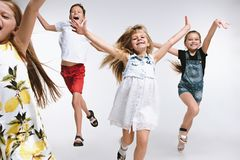 Group fashion cute preschooler kids friends posing together and looking at camera white background. Group of fashion cute preschooler kids friends running royalty free stock images