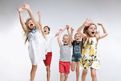 Group fashion cute preschooler kids friends posing together and looking at camera white background. Group of fashion cute preschooler kids friends running stock photo