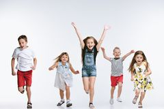 Group fashion cute preschooler kids friends posing together and looking at camera white background. Group of fashion cute preschooler kids friends running royalty free stock image