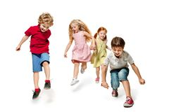 Group of fashion cute preschooler kids friends running together. And looking at camera on a white studio background. Day of book, education, school, kid royalty free stock photo