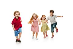 Group of fashion cute preschooler kids friends running together. And looking at camera on a white studio background. Day of book, education, school, kid royalty free stock photography