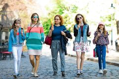 Group of fashion girls walking through downtown - having ice cre stock photography