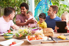 Group Of Fathers With Children Enjoying Outdoor Meal At Home Stock Photos