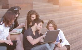 Group of fellow students with books and laptop Royalty Free Stock Image