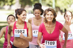 Group Of Female Athletes Competing In Charity Marathon Race Stock Images
