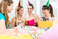 Best friends drinking champagne in front of a birthday cake. Group of female best friends drinking champagne in front of the birthday cake while celebrating stock photography