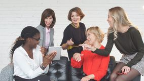 Group of female blogger professionals working at tablet sitting at table stock footage