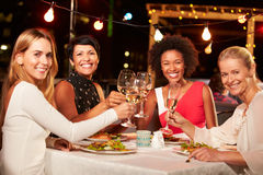 Group of female friends eating dinner at rooftop restaurant royalty free stock photography