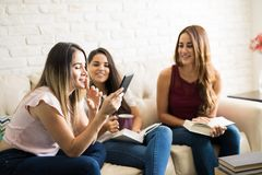 Friends having fun in a book club. Group of female friends having some fun while reading in their book club reunion Stock Photos