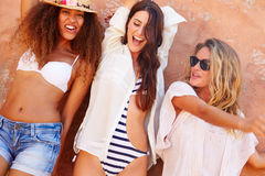 Group Of Female Friends On Holiday Together Posing By Wall Stock Images