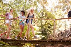 Group Of Female Friends On Walk Crossing Wooden Bridge Stock Image