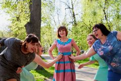 Group of female friends walking in the park. Group of female friends walking in summer or spring park. Women and adult girl have fun together outdoor stock photos