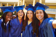 Group Of Female High School Students Celebrating Graduation. Wearing Blue Cape And Mortar