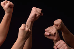 Group of female and male hands showing fists raised up on black Stock Image