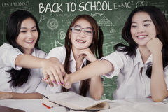 Group of female students stacking hands in class Stock Photography