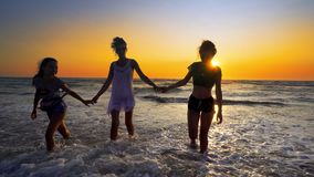 Group of female teens having fun jumping and splashing down the beach. At sunset royalty free stock photography