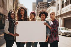 Female protesters with blank banner. Group of females protesters on road with a blank signboard. Females holding blank banner during a protest stock image