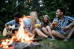 Happy friends enjoying music near campfire at night. Group of fiends enjoying music near campfire at night stock images