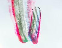 Group of fighter jet airplane with a trace of colorful smoke against sky. Stock Photos