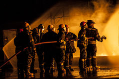 Group of firefighters fighting a burning fire Royalty Free Stock Image