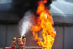 Group of firefighters man are inject spray the water to fire acc Stock Images
