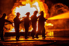 A Group of firefighters moving towards fire with hose Stock Photos