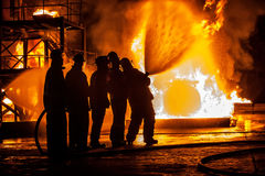 A Group of firefighters spraying a fire with water Royalty Free Stock Photos