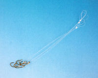 Group of fish hooks on a graduated blue background Stock Images