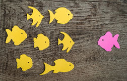 Group of fish with one pointed against the flow. On wooden background royalty free stock photos
