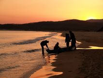 Group of fisherman on coast. Group of fisherman with boat on outward-bound against purple sunset on the sand sea beach Stock Images