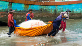 Group of fisherman pull fish net