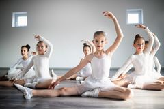 Group of fit happy children exercising ballet in studio together. Group of fit children exercising ballet in studio together royalty free stock photography