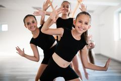 Group of fit happy children exercising ballet and dancing in studio together. Group of fit children exercising ballet and dancing in studio together royalty free stock photo