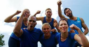 Group of fit people cheering together in boot camp 4k. Group of fit people cheering together in boot camp on a sunny day 4k stock video