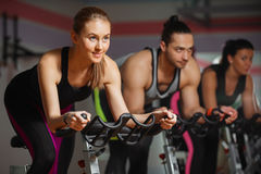 Group of fit people cycling in fitness club Stock Photo