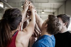 Fit People Giving High Five To Each Other In Gymnasium. Group of fit people giving high five to each other in gymnasium stock image
