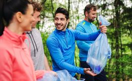 Group of fit people picking up litter in nature, a plogging concept. A roup of fit young people picking up litter in nature, a plogging concept stock image