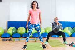 Group of fit women exercising doing squatting exercises working out their leg muscles in fitness studio.  Stock Photos