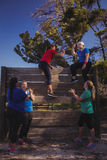 Group of fit women giving high five to each other during obstacle course training Royalty Free Stock Images