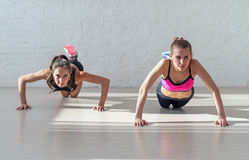 Group of fit women warming up and doing push ups. Working at gym fitness, sport, training, diet and lifestyle concept Royalty Free Stock Photo