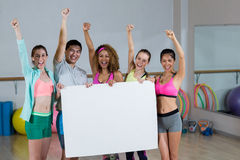 Group of fitness team holding blank placard and clenching fists. Portrait of group fitness team holding blank placard and clenching fists in fitness studio Royalty Free Stock Image