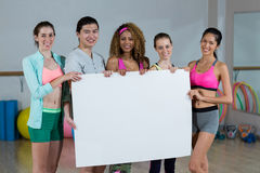 Group of fitness team holding blank placard. Portrait of group fitness team holding blank placard in fitness studio Royalty Free Stock Image