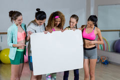 Group of fitness team holding blank placard. In fitness studio Stock Image