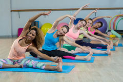 Group of fitness team performing stretching exercise Royalty Free Stock Images